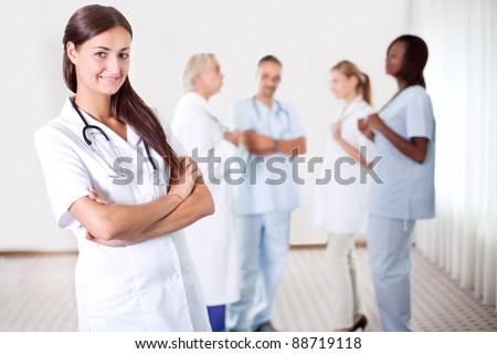 Friendly female doctor with folded hands smiling at the camera with colleagues discussing in the background