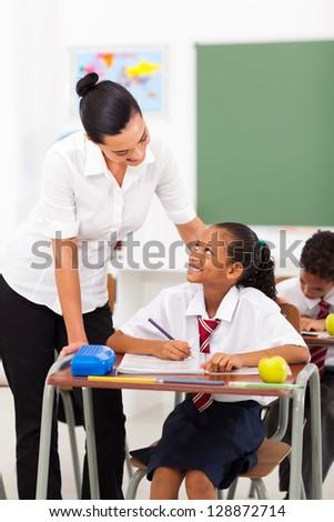 friendly female elementary school teacher talking to student in classroom