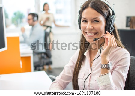 Friendly female helpline operator with headphones in call center Сток-фото ©