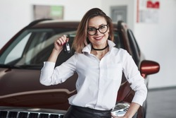 Friendly female manager stands against red car in automobile salon.