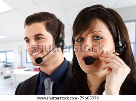 Friendly female phone operator helping a customer. Male workmate in the background.