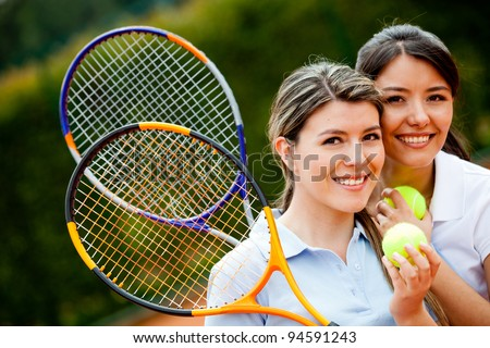 Friendly female tennis players holding rackets and smiling