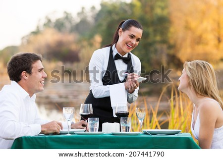 friendly female waitress taking order from cute young couple