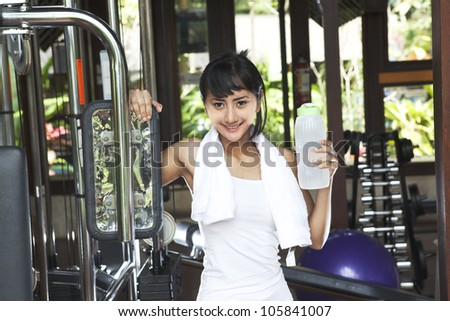 Friendly fitness young woman holding a bottle of water and smiling at the gym