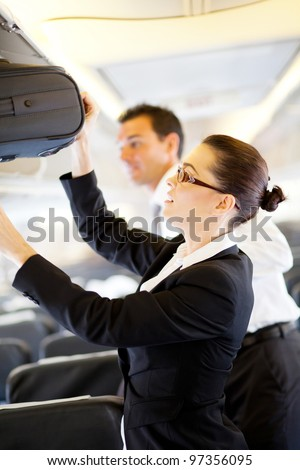 friendly flight attendant helping passenger with carry on luggage - stock photo