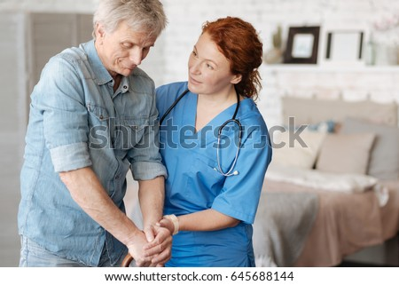 Friendly focused nurse encouraging her elderly patient #645688144