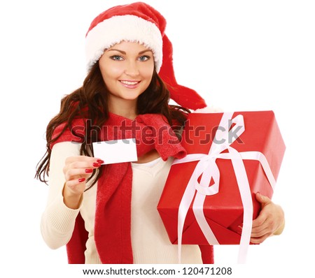 Friendly girl in santa hat with xmas gift showing blank business card isolated on white background