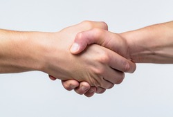 Friendly handshake, friends greeting, teamwork, friendship. Close-up. Rescue, helping gesture or hands. Strong hold. Two hands, helping hand of a friend. Handshake, arms friendship