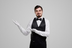 Friendly handsome bearded well dressed waiter in bow tie and gloves inviting guests to restaurant while standing against gray background
