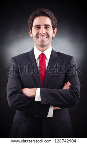 Friendly handsome businessman standing on black background