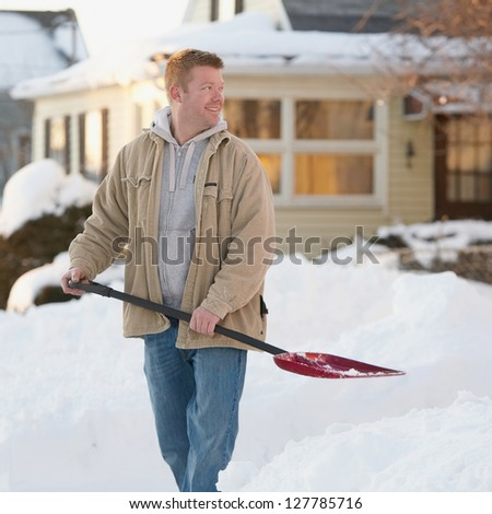 Friendly handsome man shoveling snow
