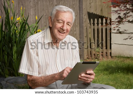Friendly handsome old man with tablet computer