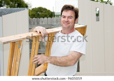 Friendly handyman carrying a ladder and smiling.