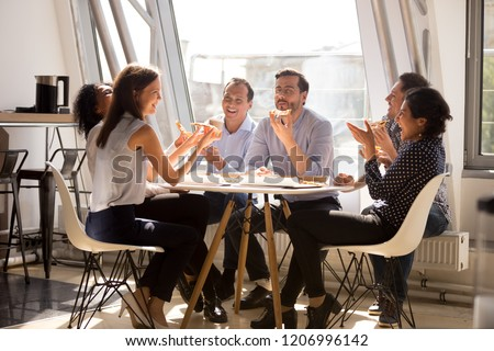 Friendly happy diverse team workers talking laughing eating pizza together in office, cheerful workers staff group chatting sharing meal enjoying having fun at work, good relations at lunch break