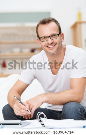 Friendly happy good looking man in glasses relaxing in his living room working on paperwork and his accounts looking up to smile at the camera