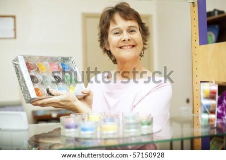 Friendly, happy store clerk holding up a gift set of candles.