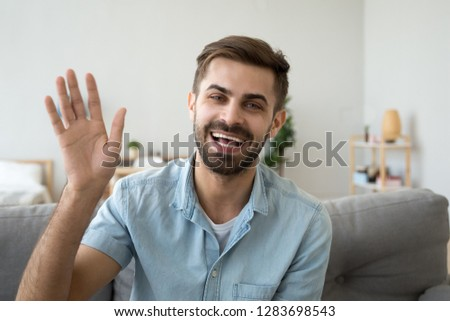 Friendly happy young man waving hand saying hello looking at camera greeting distant friend making online call, cheerful male vlogger blogger recording vlog teaching e-coaching via webcam, portrait