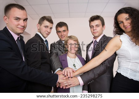 Friendly harmonious business team. Six business people join hands and smiling. Focus is on hands, but face expression is recognizable