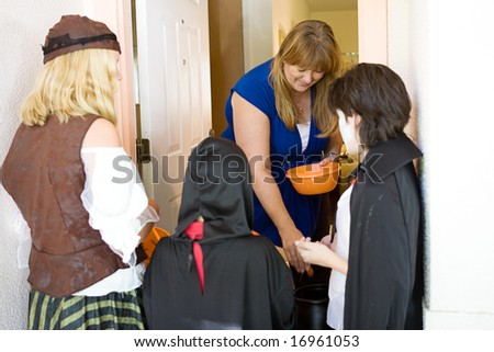Friendly homeowner passing out candy to trick or treaters on Halloween.