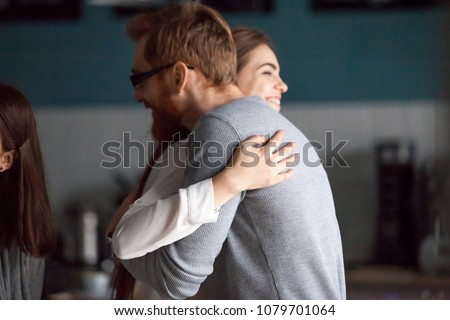 Friendly hug concept, smiling millennial man and woman embracing glad to see each other greeting at meeting, young guy and girl cuddling expressing care, friendship and good warm relations concept
