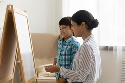 Friendly indian woman psychologist and small boy stand by easel board hold crayon planning picture talk on visual art therapy session. Happy hindu mother teach little son to draw using piece of chalk