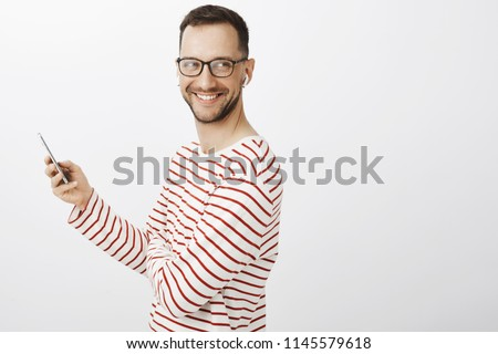 Friendly joyful adult coworker with bristle, wearing trendy black eyewear and striped pullover, looking right and smiling broadly while listening music in wireless earbuds and holding smartphone