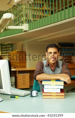 Friendly librarian sitting at desk with books