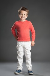 Friendly little five year old boy posing over gray background.