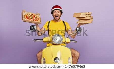 Friendly looking delighted delivery man holds cardboard boxes, one opened container with delicious pizza, transports food items from cafe to clients, brings orders by motorbike, likes his job #1476079463