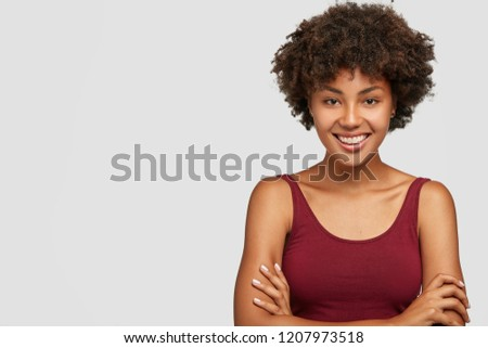 Photo of Friendly looking self assured dark skinned young girl keeps arms folded, has toothy smile, dressed in casual clothes, models against white background with free space for your promotional content