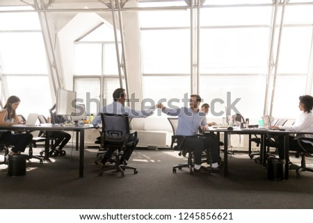 Friendly male colleagues fist bumping at workplace, celebrating good teamwork results, corporate success, employees share success, diverse office worker team at work in modern office, respect concept