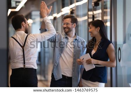 Friendly male colleagues giving high five talking standing in office hall, smiling businessmen diverse professionals group greeting meeting in company hallway work space express respect agreement