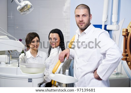 Friendly male dentist, assistant and smiling patient at dental clinic