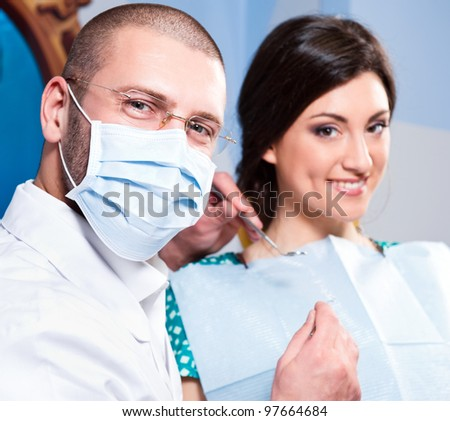 Friendly male dentist with smiling patient at dental clinic