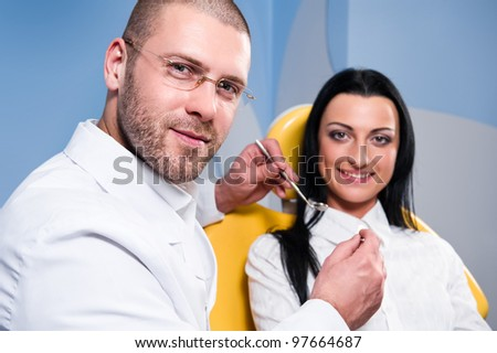Friendly male dentist with smiling patient at dental clinic - stock photo