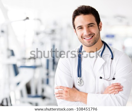 Friendly male doctor at the gym smiling - stock photo