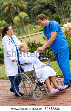 friendly male doctor greeting recovering senior patient in wheelchair outdoors