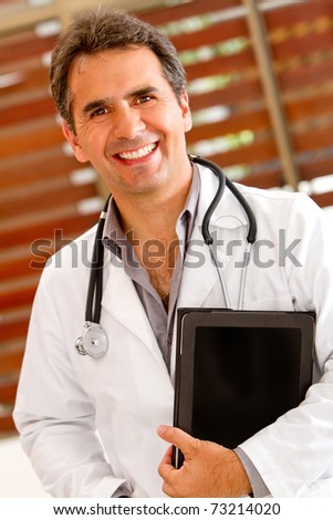 Friendly male doctor smiling at the hospital