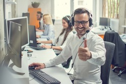 Friendly male helpline operator man with headphones showing thumb up in call center.