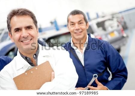 Friendly male mechanics at a car garage