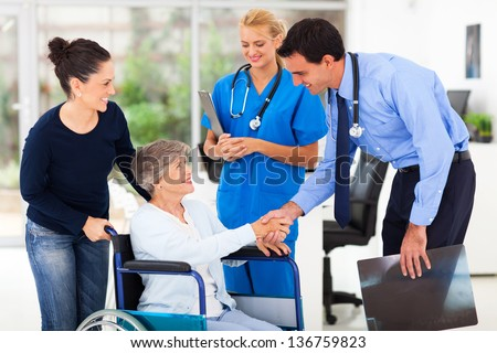 friendly male medical doctor greeting senior patient