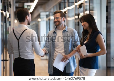 Friendly male professional colleagues greeting handshaking meeting in company office hall, smiling businessmen shaking hands starting teamwork partnership standing in corporate work space hallway