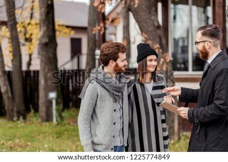 Friendly male real estate agent in formal wear standing outdoor, in front of the private house, handing house key to a young excited couple dressed in warm autumn clothes #1225774849