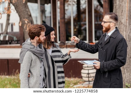 Friendly male real estate agent in formal wear standing outdoor, in front of the private house, handing house key to a young excited couple dressed in warm autumn clothes #1225774858