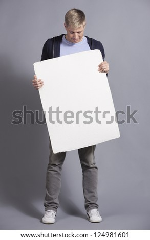 Friendly man looking at white empty signboard with space for text while holding it, isolated on grey background.