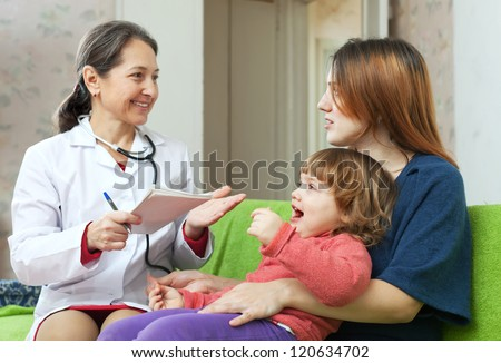 friendly mature children's doctor examining baby in home