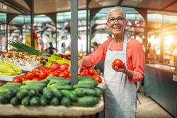 Friendly mature woman tending an organic vegetable stall at a farmer's market and selling fresh vegetables from the garden. Female Stall Holder At Farmers Fresh Food Market