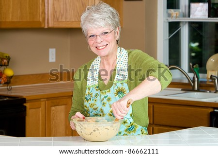 Friendly mature woman with a nice smile and white hair baking cookies in the kitchen.