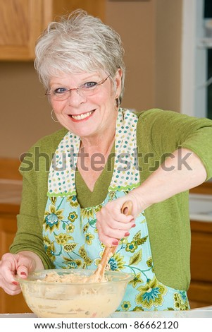 stock photo : Friendly mature woman with a nice smile and white hair baking ...
