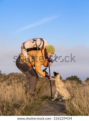 Friendly meeting on the trail. Female hiker meets friendly dog on her trail. They introduce themselves to each other and shake hands.